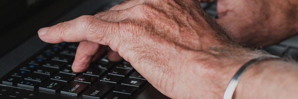 Gigtfingre der skriver på et tastatur