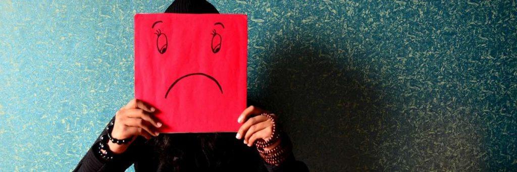Person med et skilt med en sur smiley