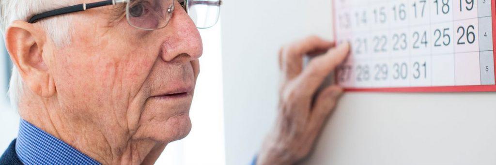 Ældre mand der peget på en vægkalender