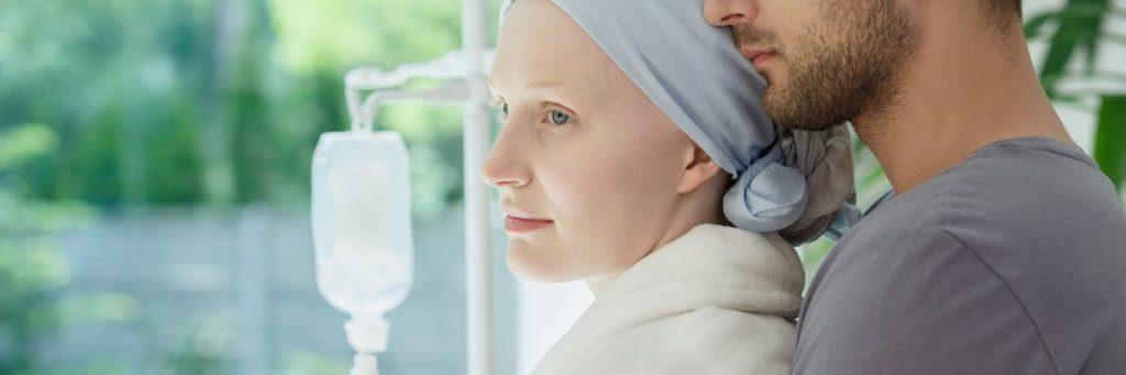 Kræftramtkvinde omfavnet af sin mand